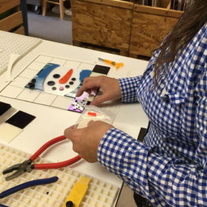 Student assembling snowman cookie tray fused project